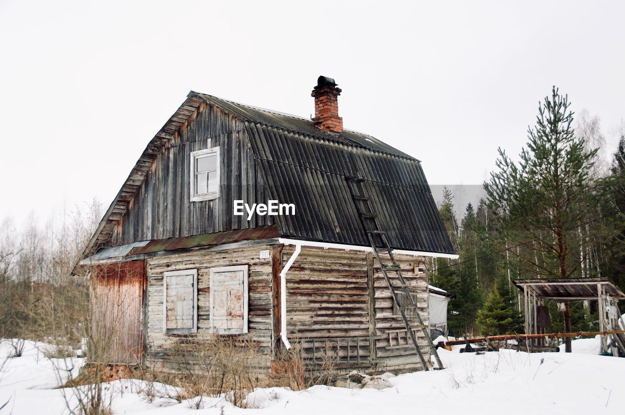 snow, winter, cold temperature, built structure, building exterior, architecture, sky, nature, building, day, field, house, plant, tree, land, covering, wood - material, abandoned, clear sky, no people, outdoors, cottage
