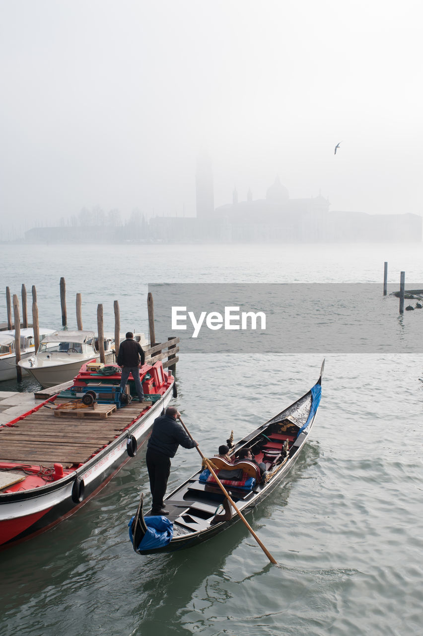 Rear View Of Men On Gondola At San Giorgio Maggiore During Foggy Weather
