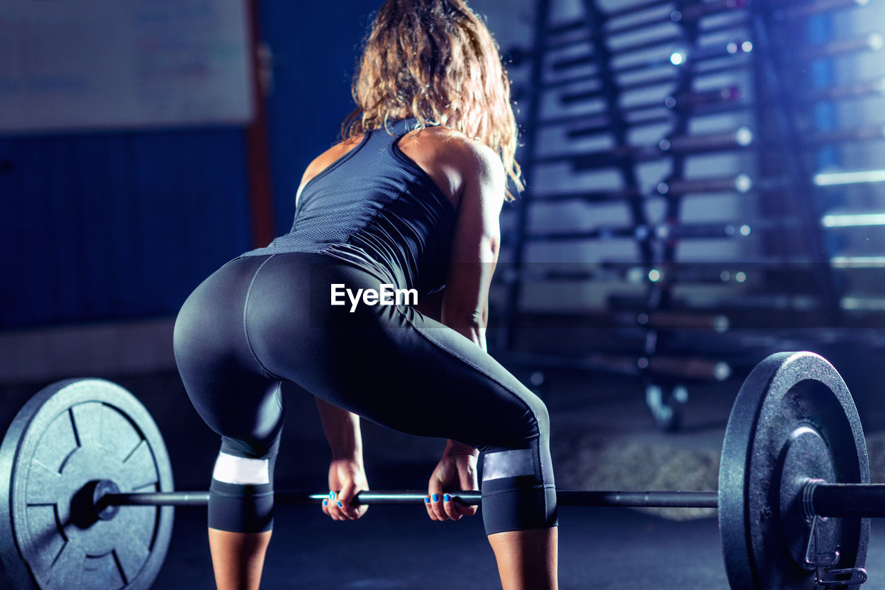 muscular build, sports training, strength, exercising, healthy lifestyle, weight, sport, weight training, gym, vitality, weights, lifestyles, wellbeing, effort, exercise equipment, sports clothing, women, indoors, athlete, sports equipment, equipment, body conscious, hairstyle, dumbbell, hair