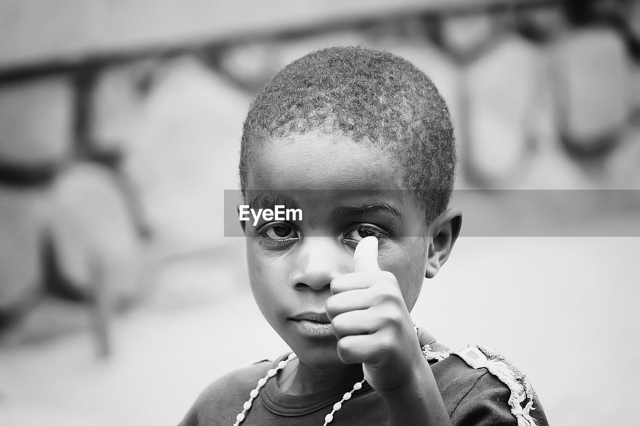 childhood, boys, focus on foreground, one person, real people, elementary age, front view, headshot, holding, close-up, one boy only, lifestyles, portrait, looking at camera, day, outdoors, people