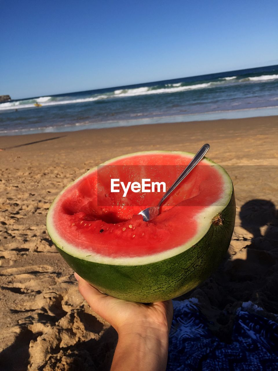 fruit, healthy eating, food and drink, beach, freshness, watermelon, holding, slice, sea, shore, human hand, sand, real people, one person, refreshment, nature, food, healthy lifestyle, human body part, lifestyles, outdoors, horizon over water, day, beauty in nature, close-up, water, sky, clear sky, people