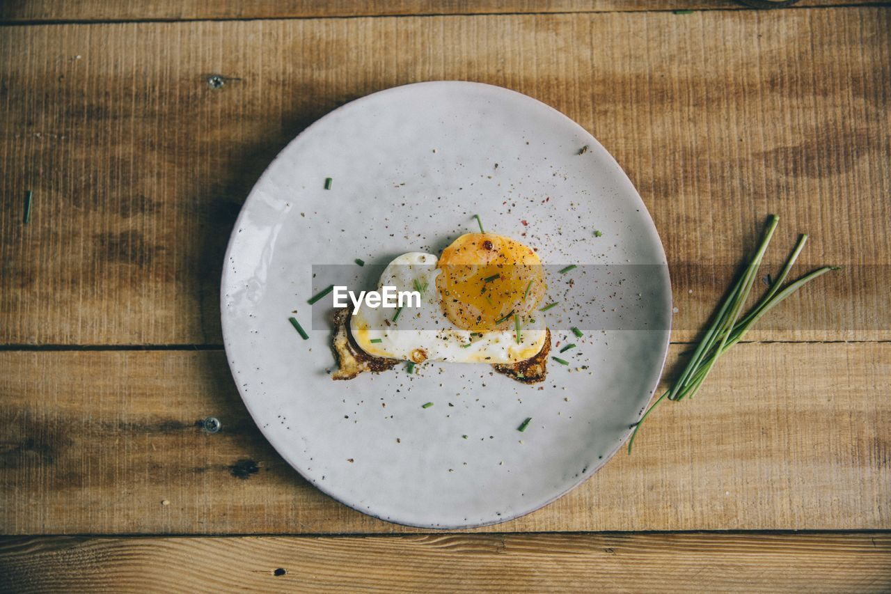food and drink, food, freshness, healthy eating, ready-to-eat, wood - material, egg, table, wellbeing, directly above, indoors, still life, meal, plate, no people, close-up, fried, high angle view, serving size, breakfast, fried egg, garnish, egg yolk