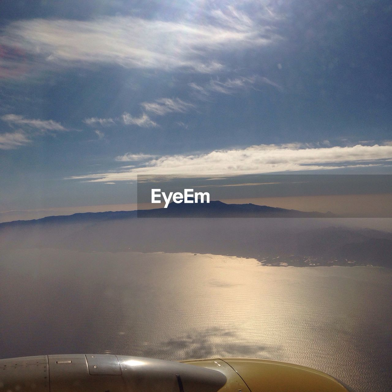 Scenic View Of El Teide Volcano Against Sky Seen From Cropped Airplane Flying Over Sea
