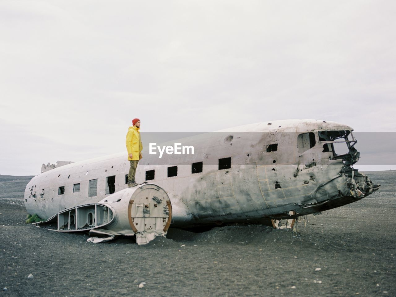 Man standing on airplane wreck against sky