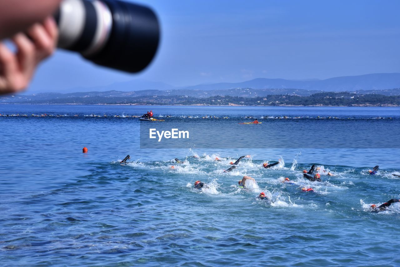 water, real people, lifestyles, sea, sport, nature, sky, people, waterfront, mountain, day, men, group of people, outdoors, beauty in nature, motion, athlete, blue, swimming