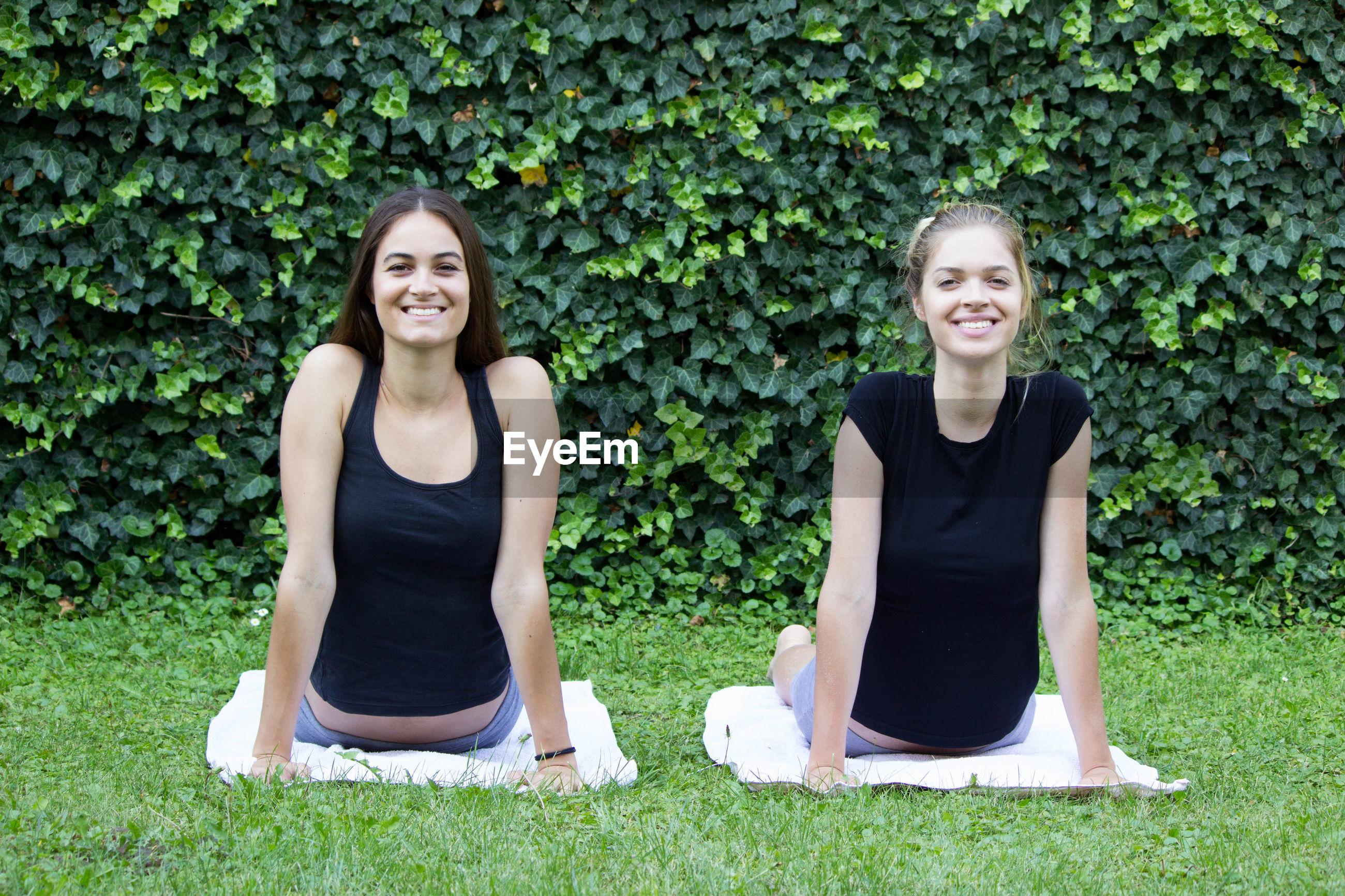 Portrait of smiling friends exercising against plants in park