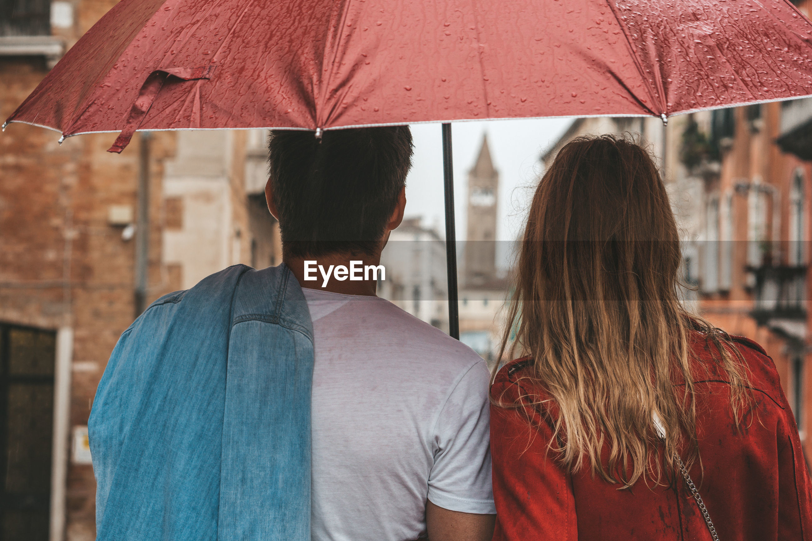 Rear view of couple standing with umbrella in city