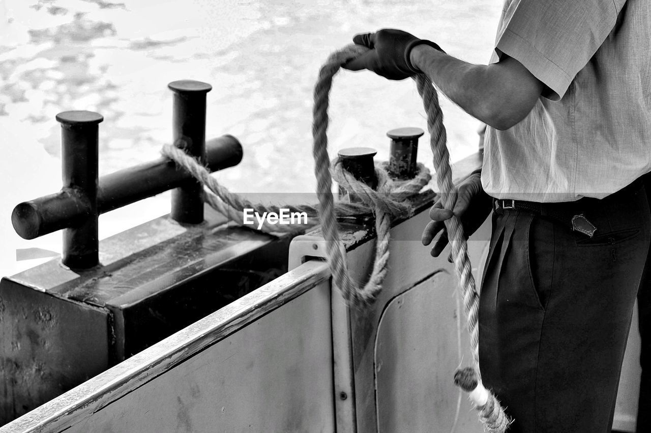 Midsection Of Man Holding Rope While Standing In Boat