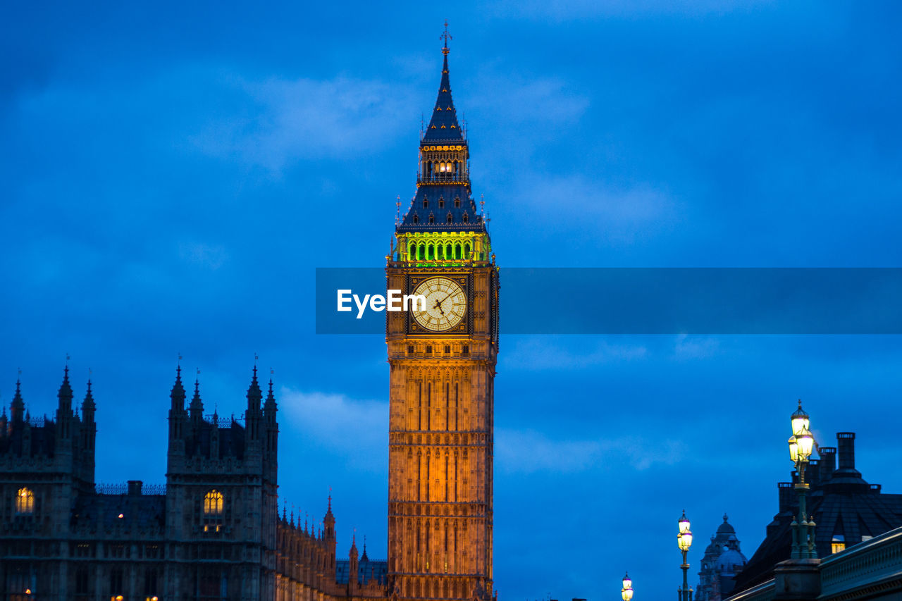 Low angle view of illuminated big ben against sky at dusk