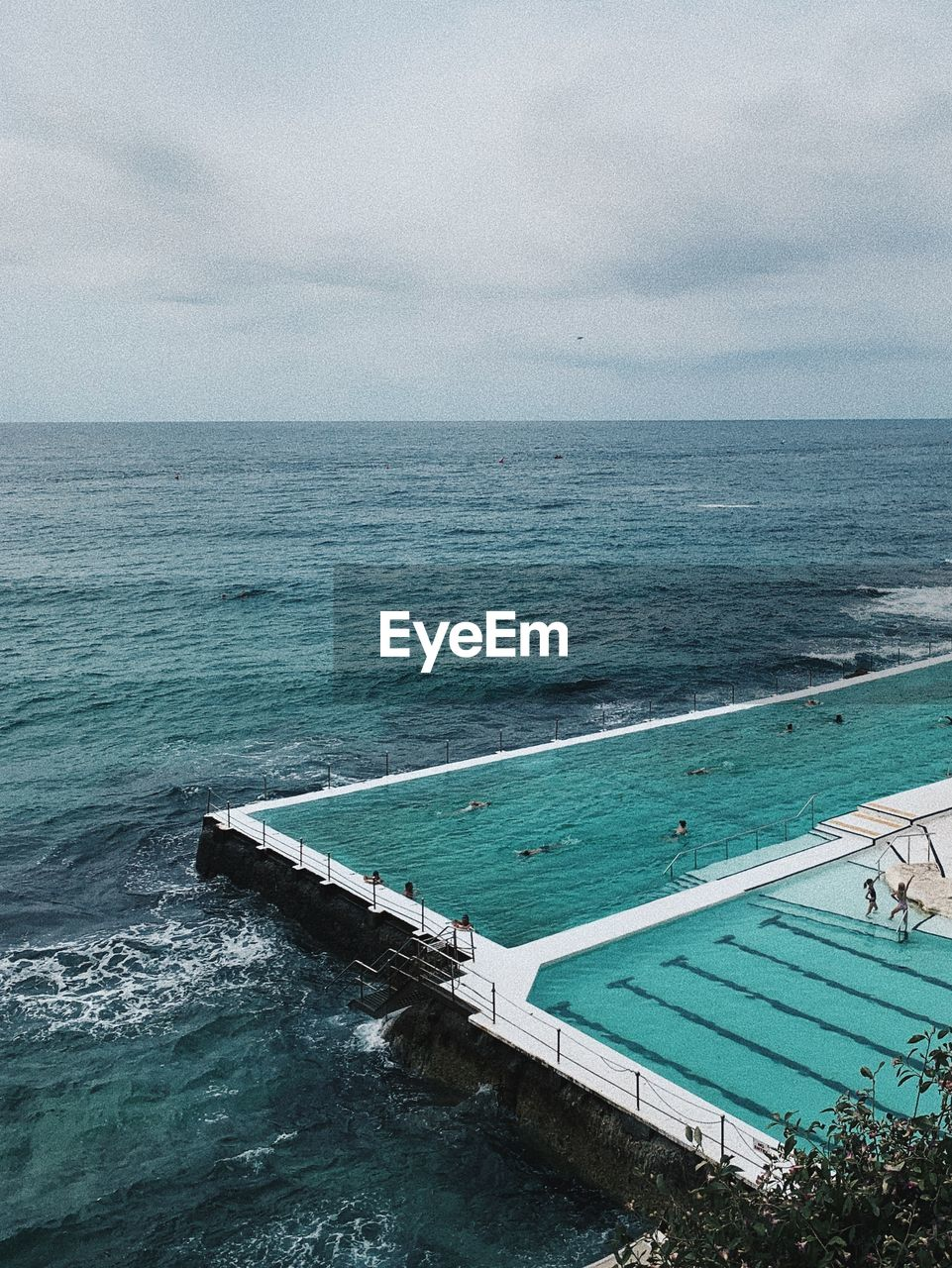 HIGH ANGLE VIEW OF SWIMMING POOL AGAINST SEA