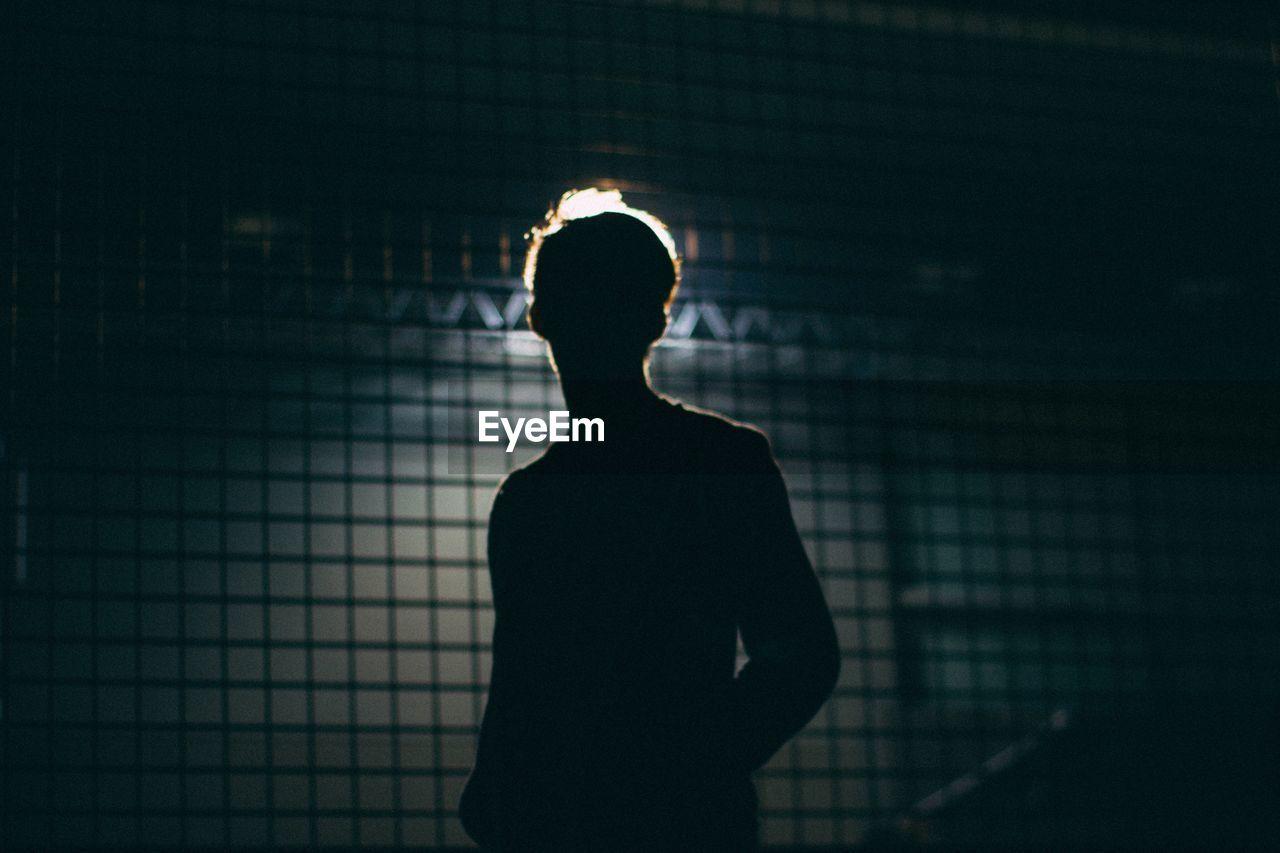 Silhouette man standing against illuminated light