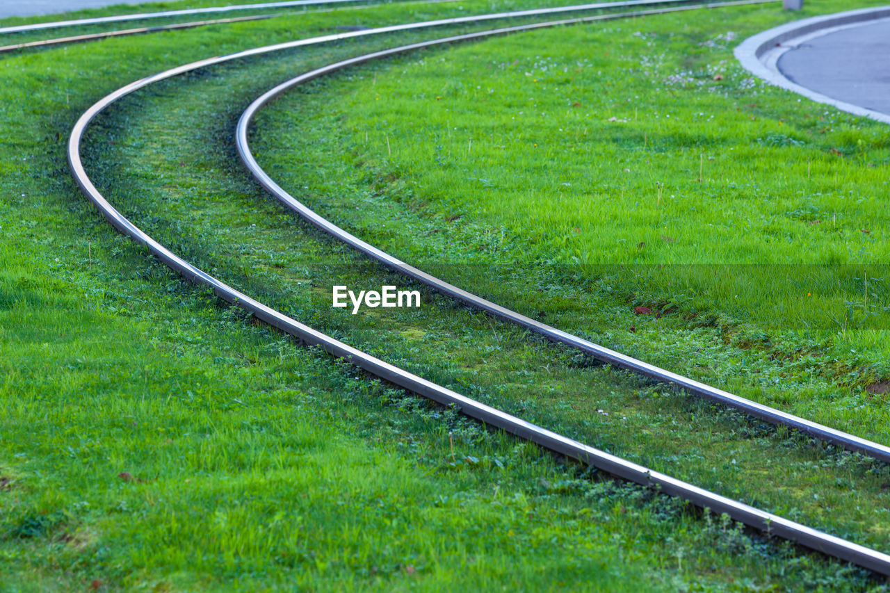 grass, plant, track, railroad track, green color, rail transportation, transportation, no people, mode of transportation, nature, land, day, curve, field, outdoors, in a row, lawn, high angle view, sport, tranquility, parallel