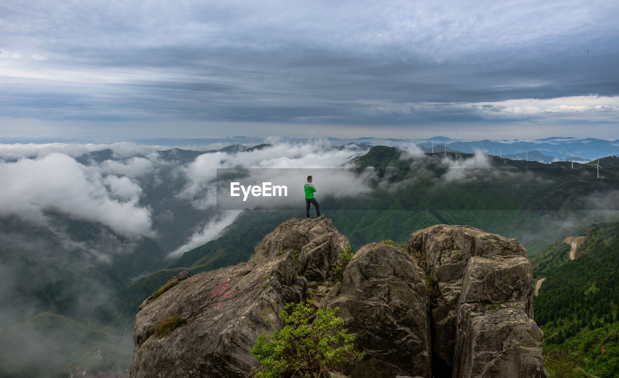 Man standing on cliff overlooking mountains and wind turbine
