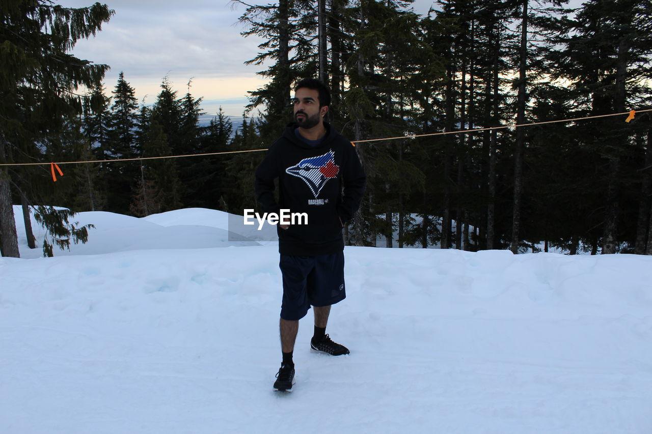 Full Length Of Man Standing On Snow Against Trees