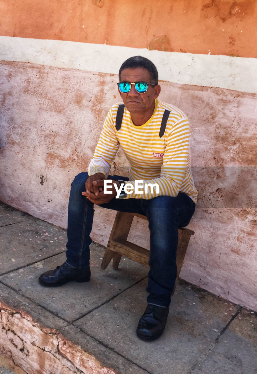 real people, casual clothing, sunglasses, one person, young adult, leisure activity, full length, front view, sitting, young men, lifestyles, mid adult men, architecture, standing, outdoors, day, eyeglasses, building exterior, built structure, cap, technology, portrait, wireless technology, young women
