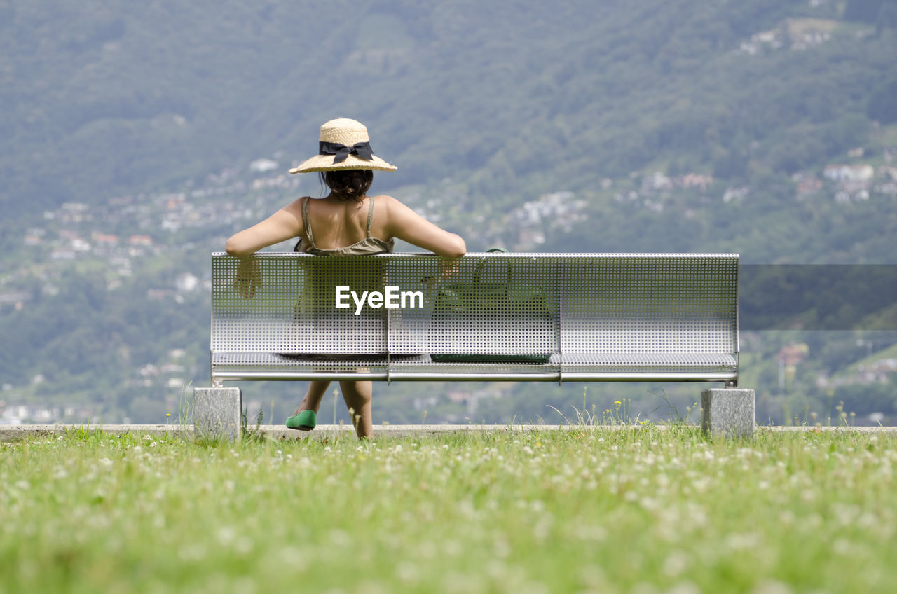 Rear View Of Woman Sitting On Bench Against Mountains At Public Park