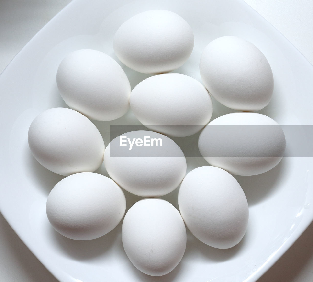 HIGH ANGLE VIEW OF EGGS IN WHITE CONTAINER