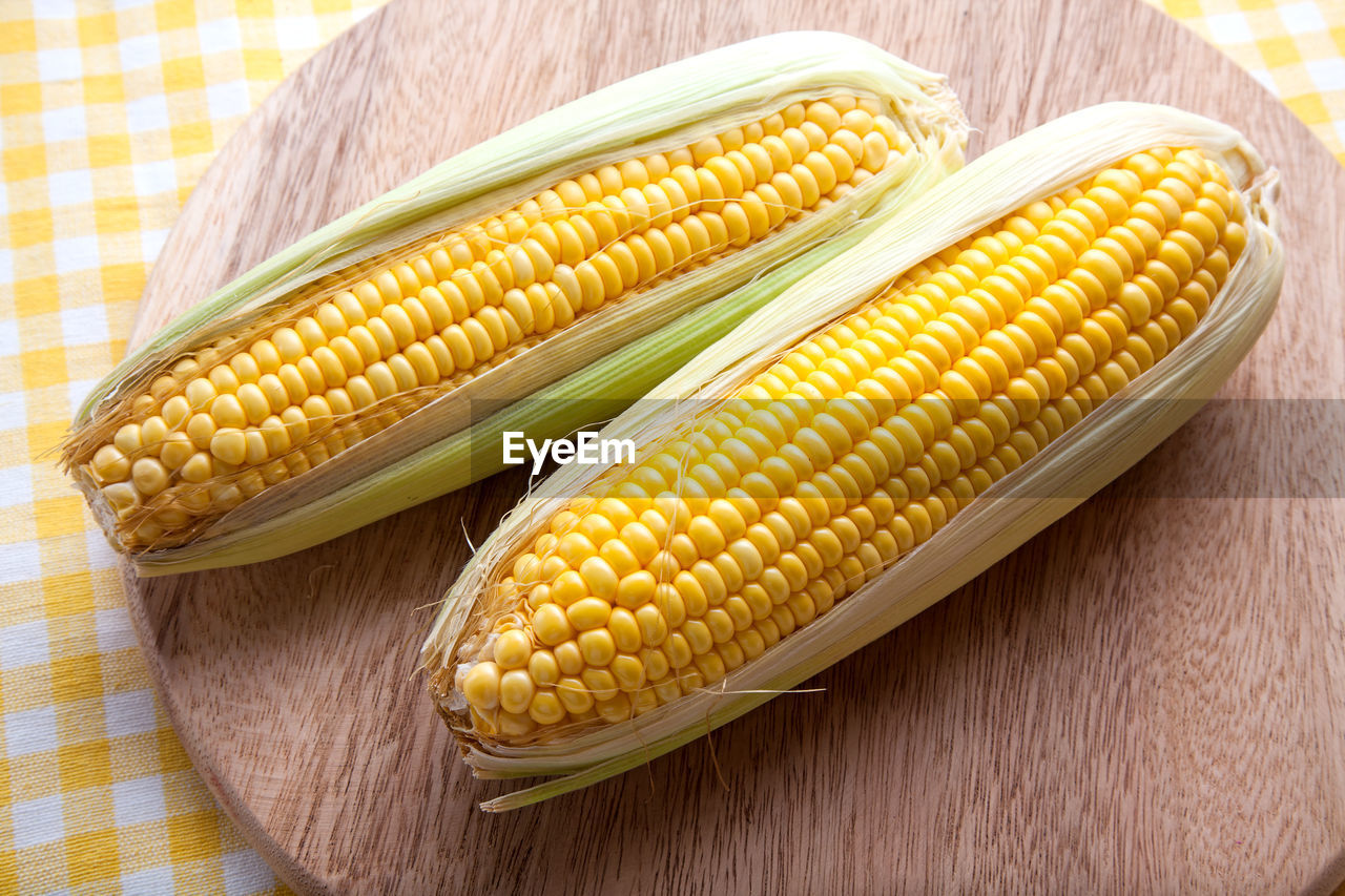 corn, food and drink, vegetable, food, healthy eating, yellow, freshness, wellbeing, sweetcorn, table, still life, corn on the cob, close-up, no people, indoors, raw food, high angle view, corn - crop, wood - material, crop, vegetarian food