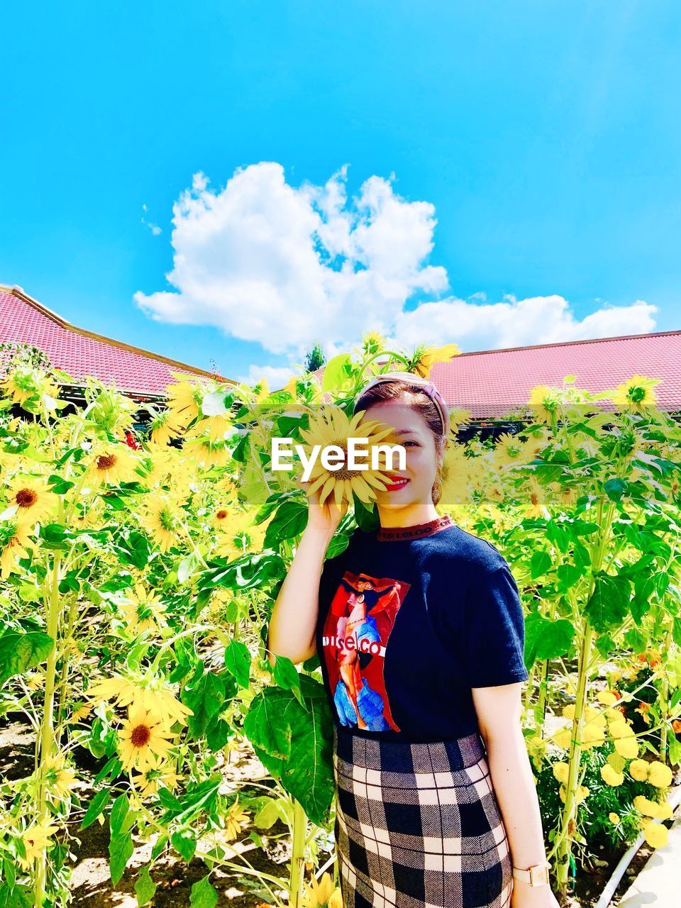 plant, young adult, one person, leisure activity, real people, young women, standing, lifestyles, growth, nature, flowering plant, flower, casual clothing, cloud - sky, beauty in nature, day, front view, sky, waist up, three quarter length, beautiful woman, outdoors, flower head, teenager