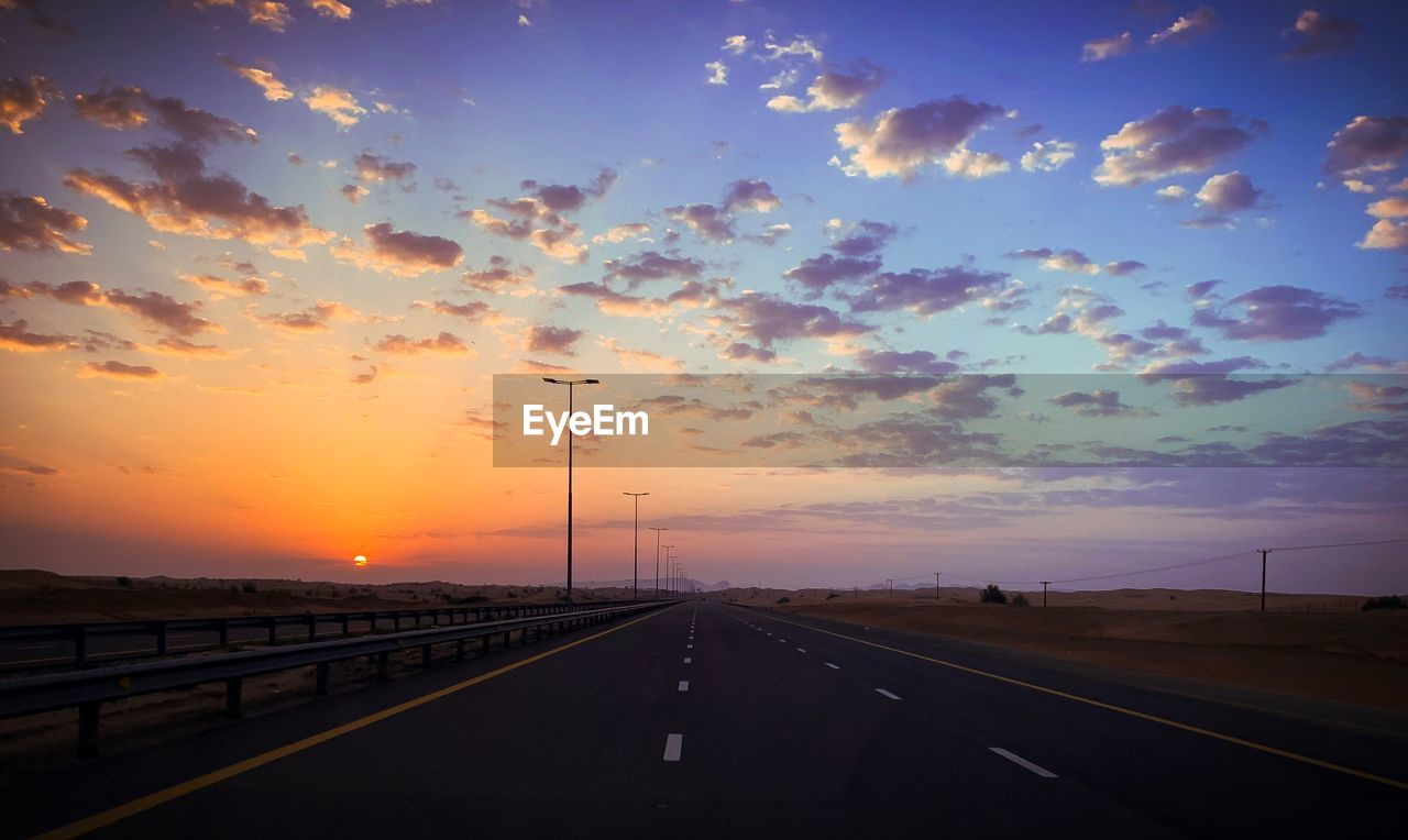 sky, sunset, transportation, road, cloud - sky, orange color, direction, nature, diminishing perspective, the way forward, street, no people, beauty in nature, city, outdoors, scenics - nature, mode of transportation, architecture, symbol, sun