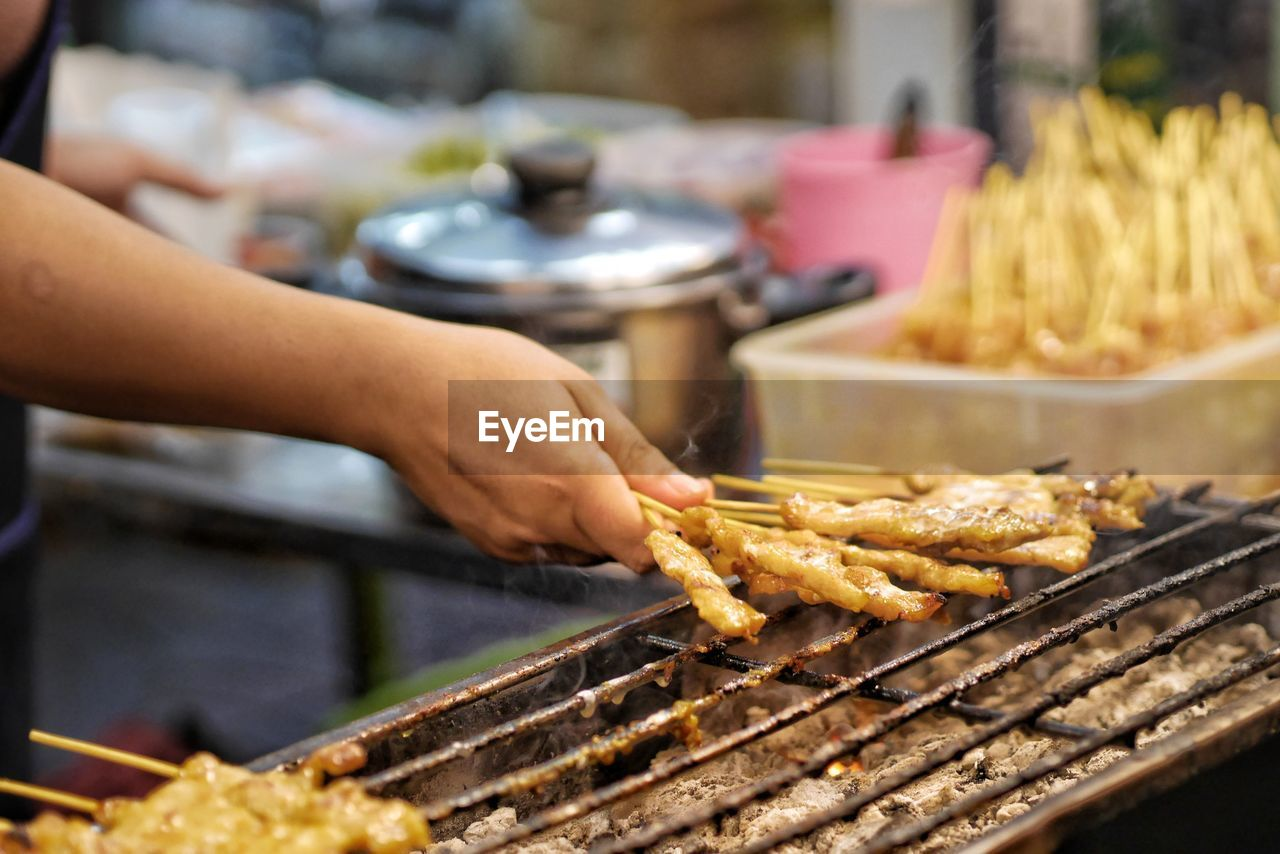 MIDSECTION OF PERSON PREPARING FOOD ON BARBECUE