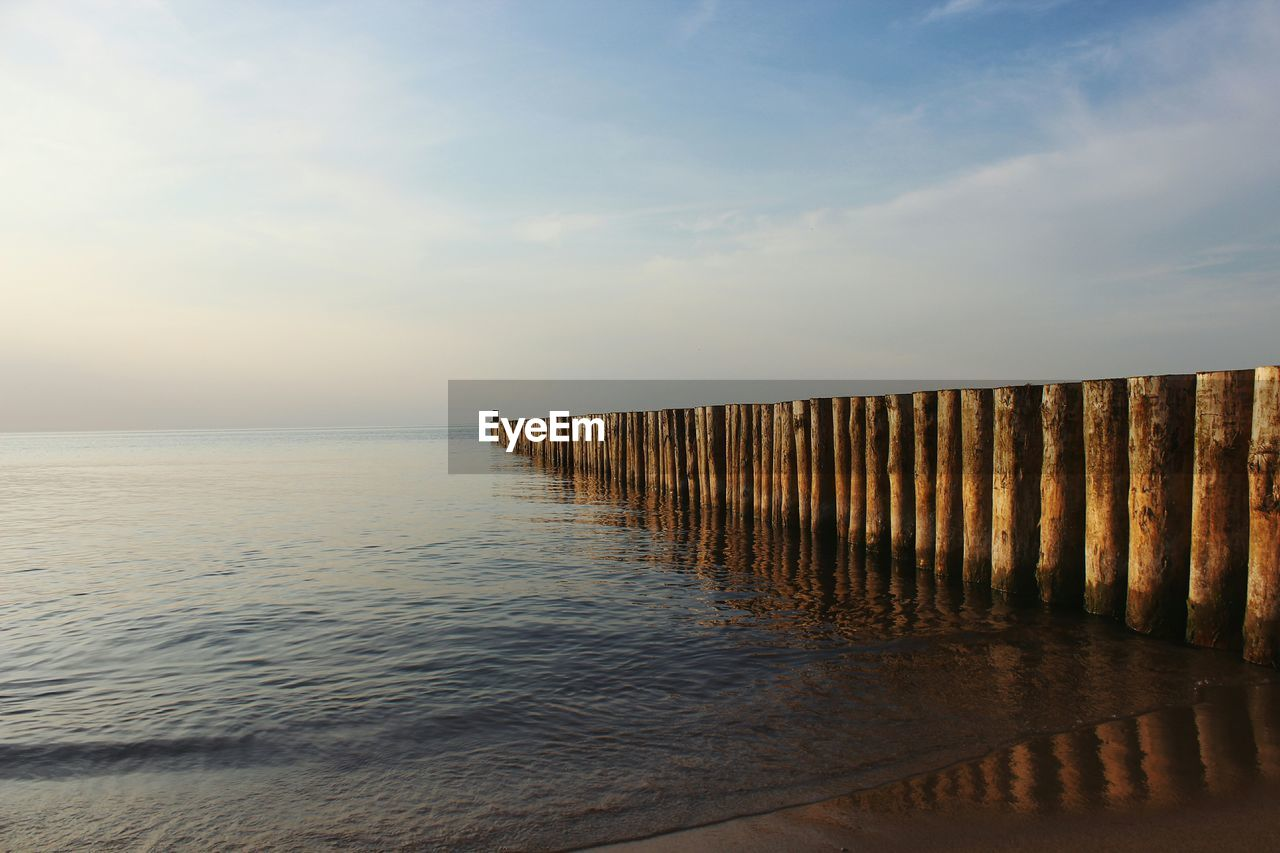 sea, water, sky, tranquil scene, tranquility, scenics, horizon over water, nature, beach, outdoors, beauty in nature, sunset, no people, cloud - sky, wooden post, day