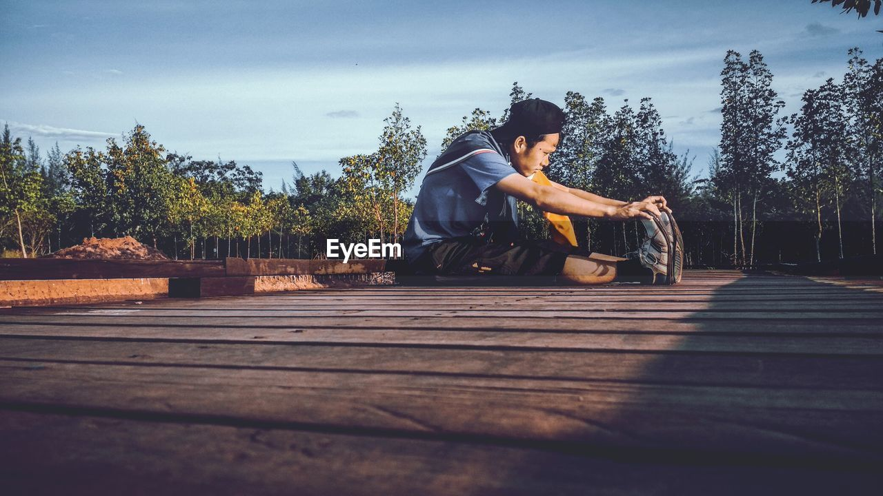 Side view of young man exercising while sitting on boardwalk against sky