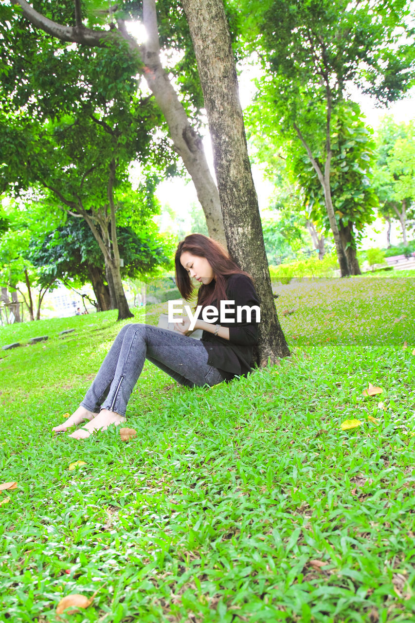 Full length of young woman reading book at park
