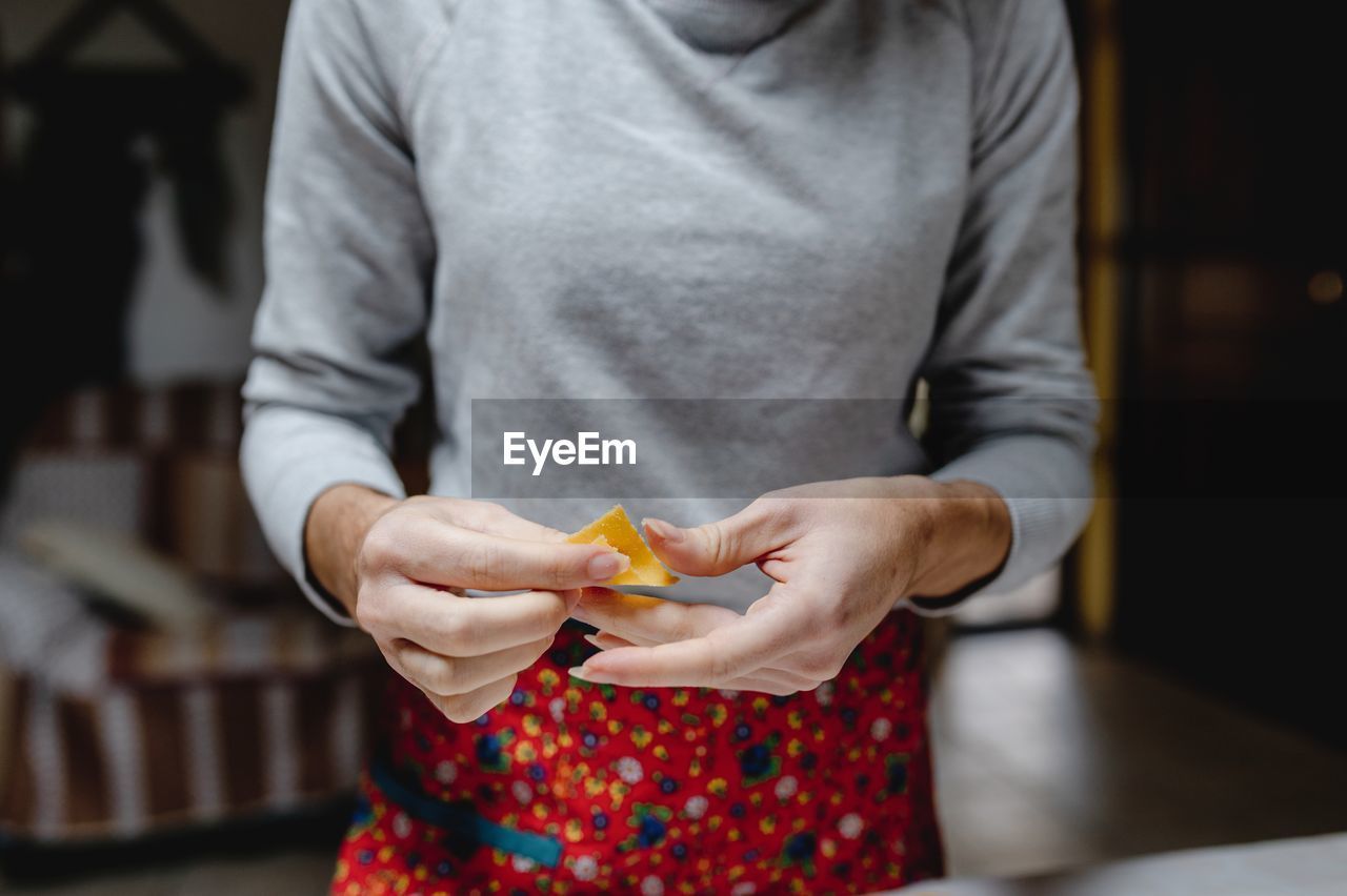 MIDSECTION OF WOMAN HOLDING FOOD