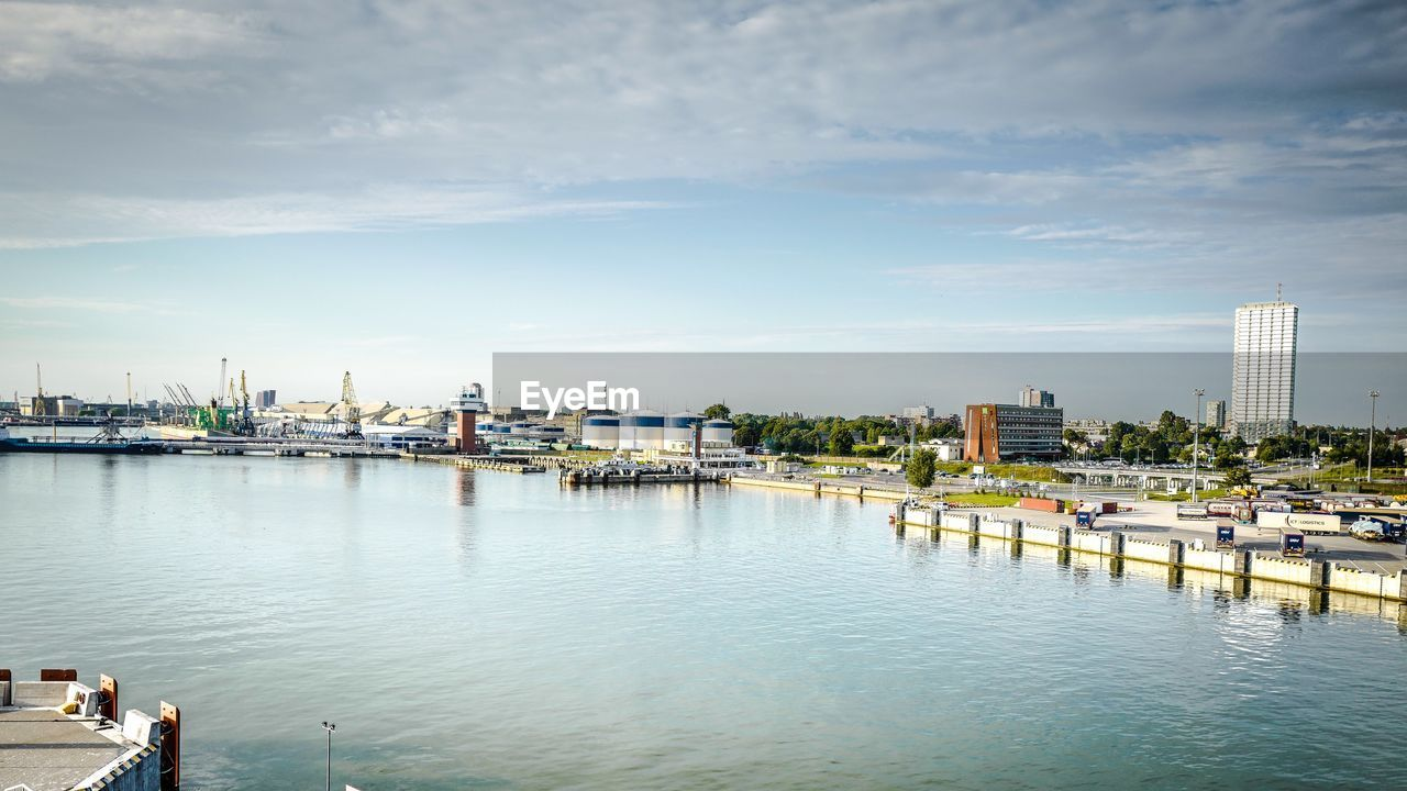 water, sky, transportation, nautical vessel, architecture, waterfront, cloud - sky, mode of transportation, nature, harbor, pier, built structure, building exterior, day, industry, sea, no people, outdoors, commercial dock, bay, yacht