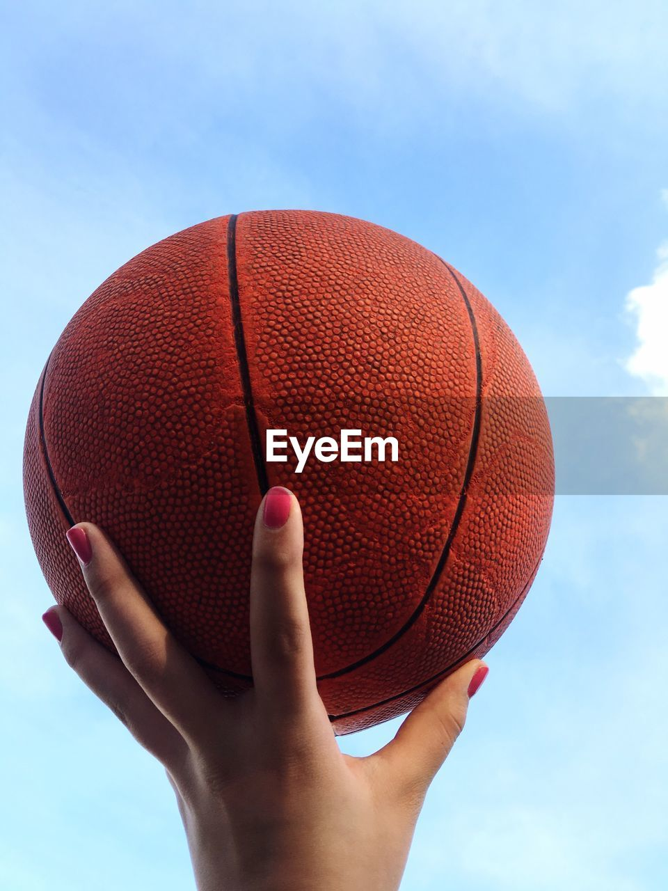 human hand, hand, sport, ball, one person, leisure activity, human body part, holding, lifestyles, real people, day, sky, unrecognizable person, red, basketball - sport, nature, cloud - sky, body part, finger, basketball - ball