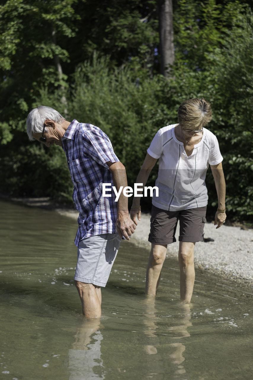 Senior Couple Enjoying In Kocher Lake Against Trees