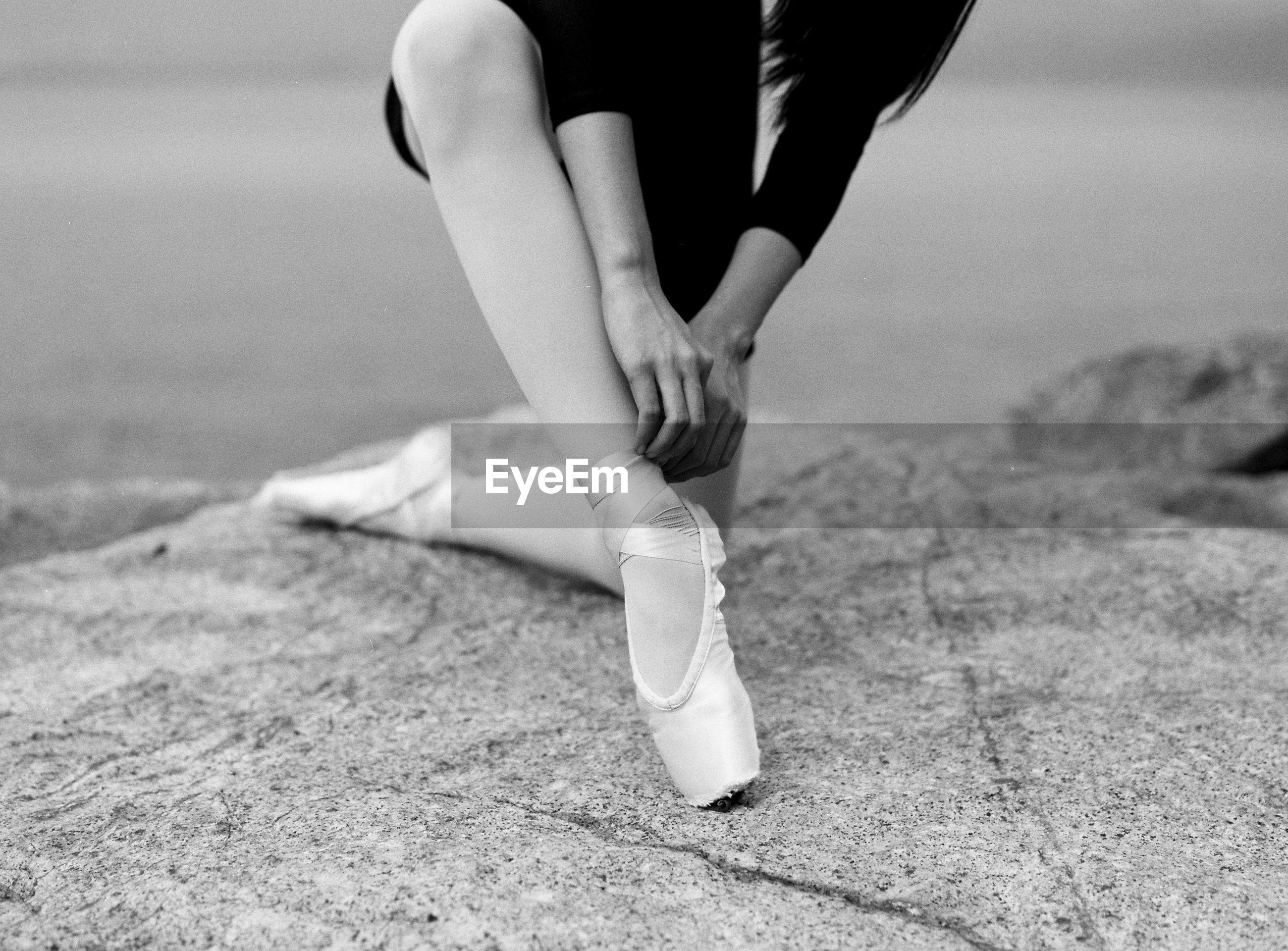 Midsection of ballerina tying shoe on rock