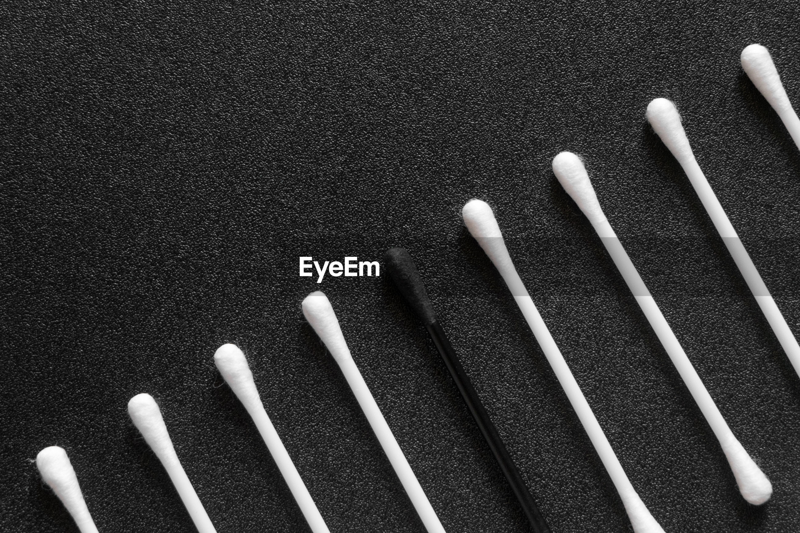 High angle view of cotton buds over black background