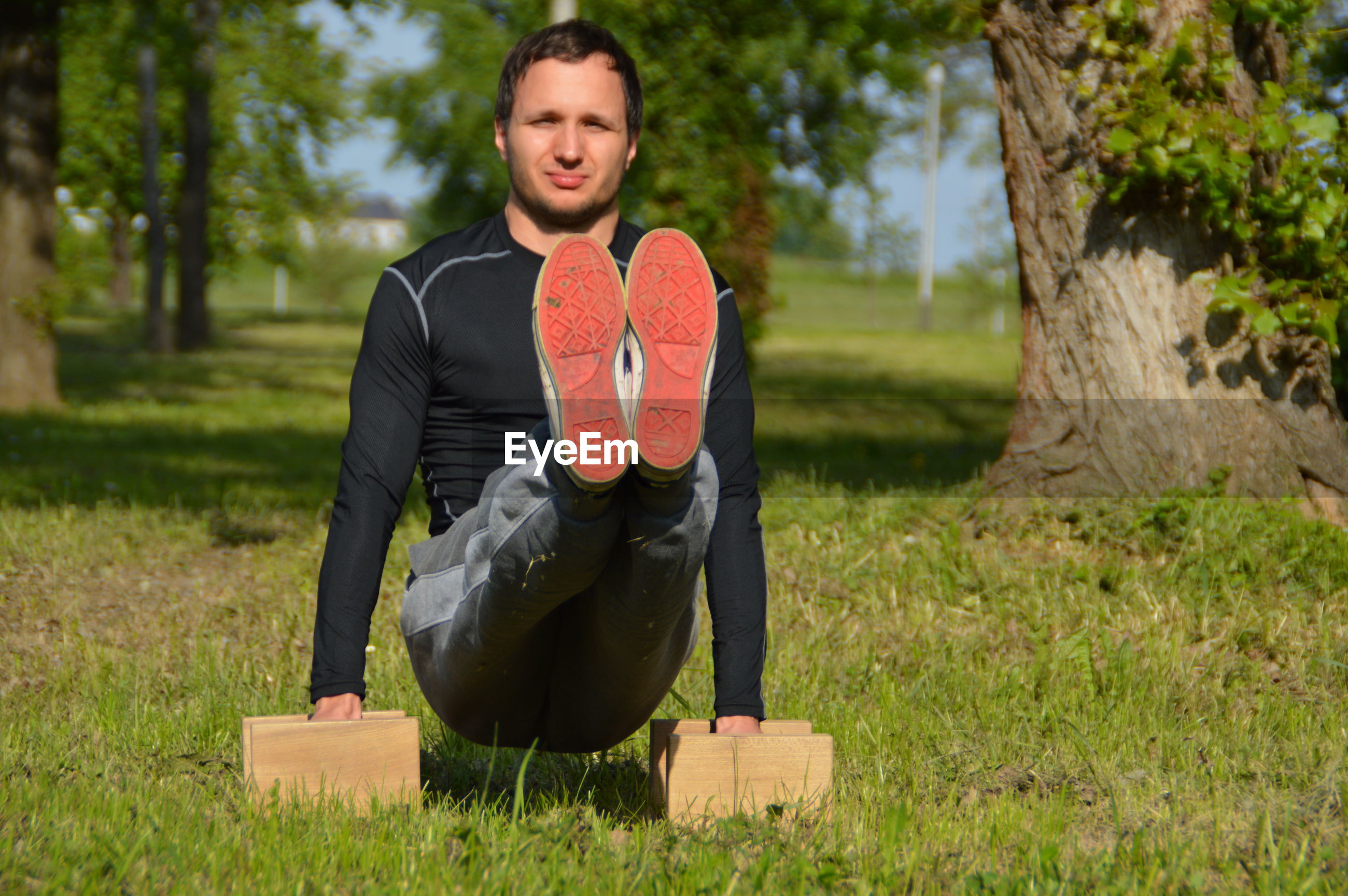 Portrait of man performing yoga in park during sunny day