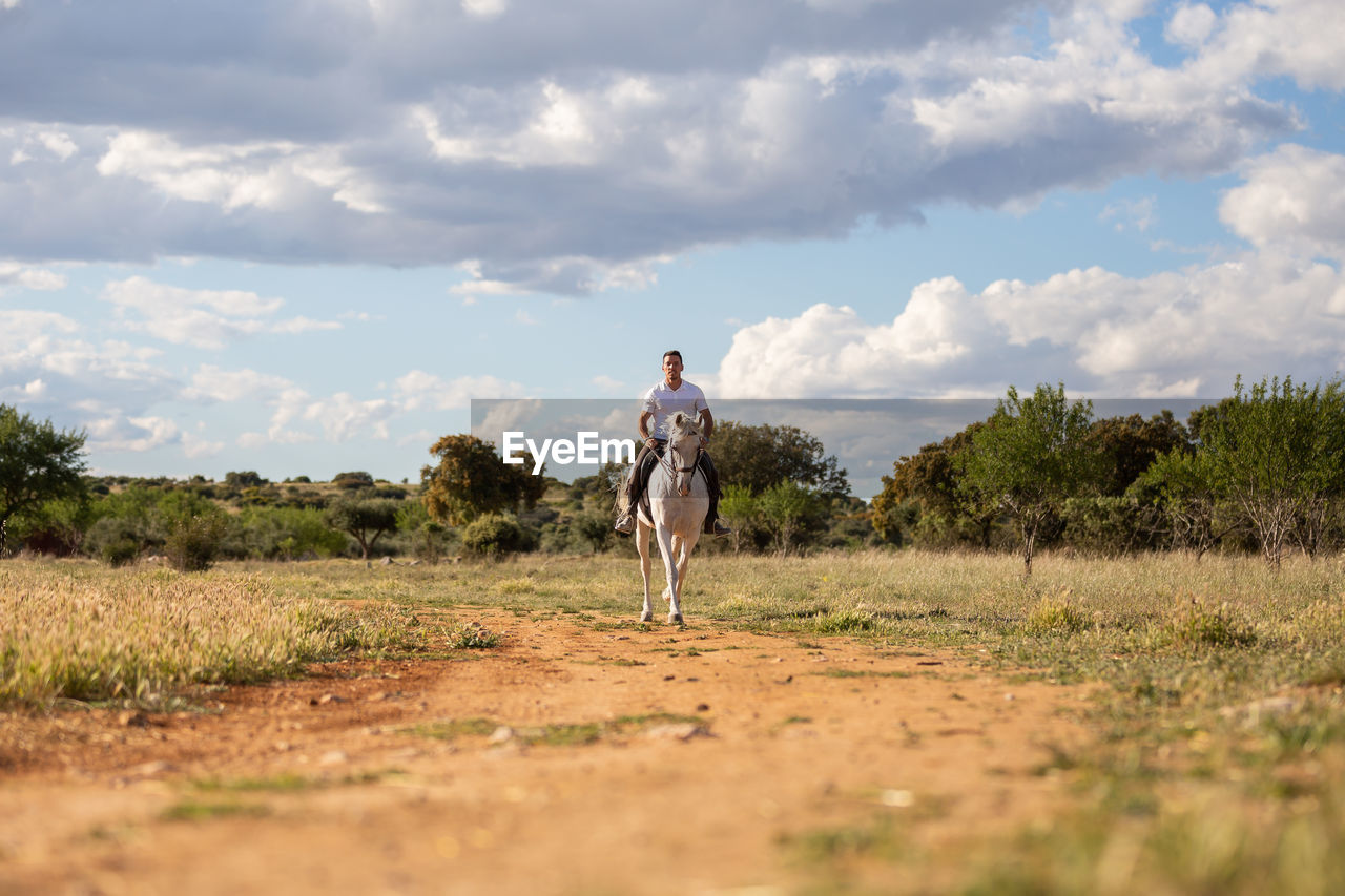 Man horse riding on land against sky
