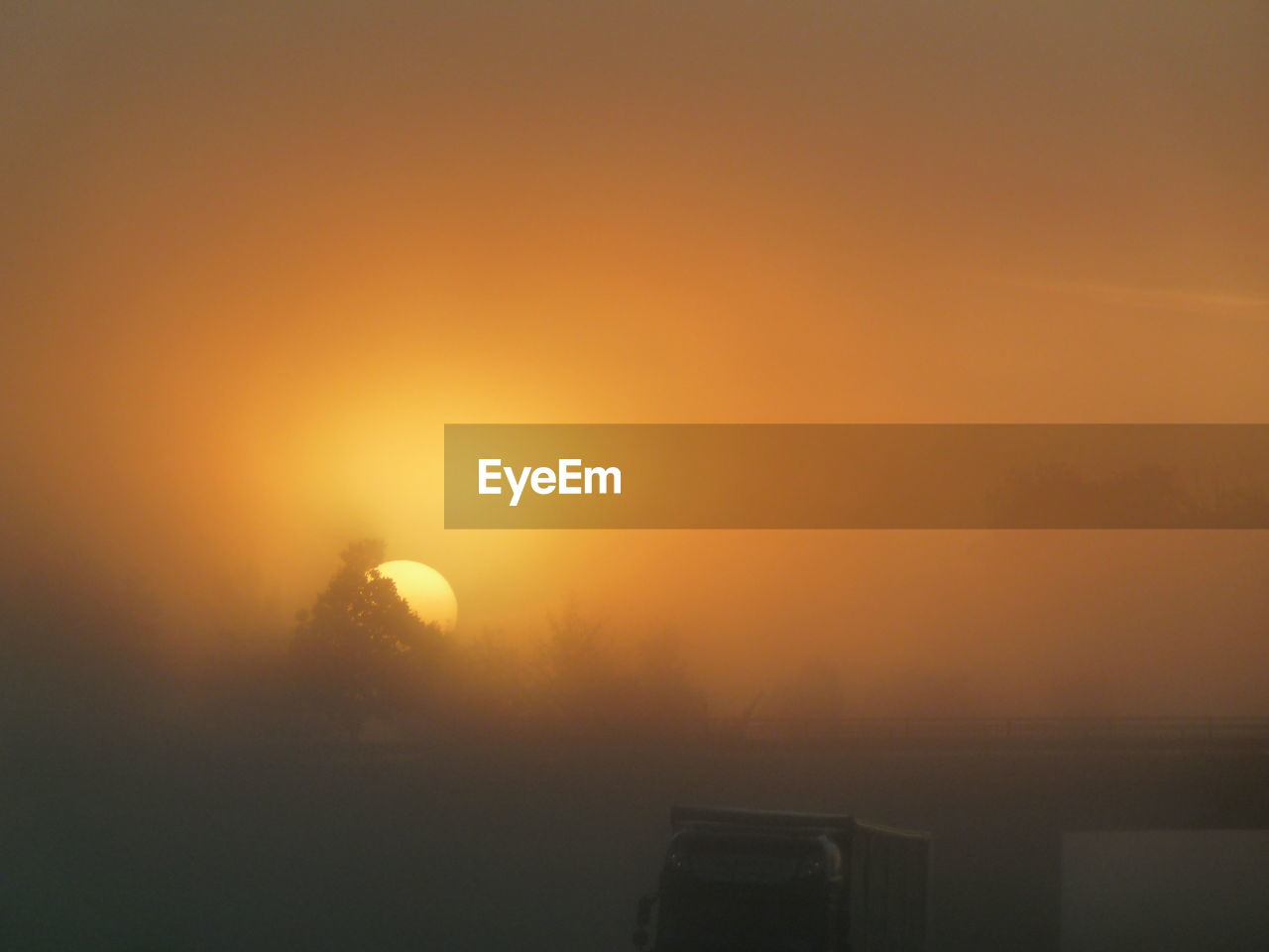 Scenic View Of Sunset On Field During Foggy Weather