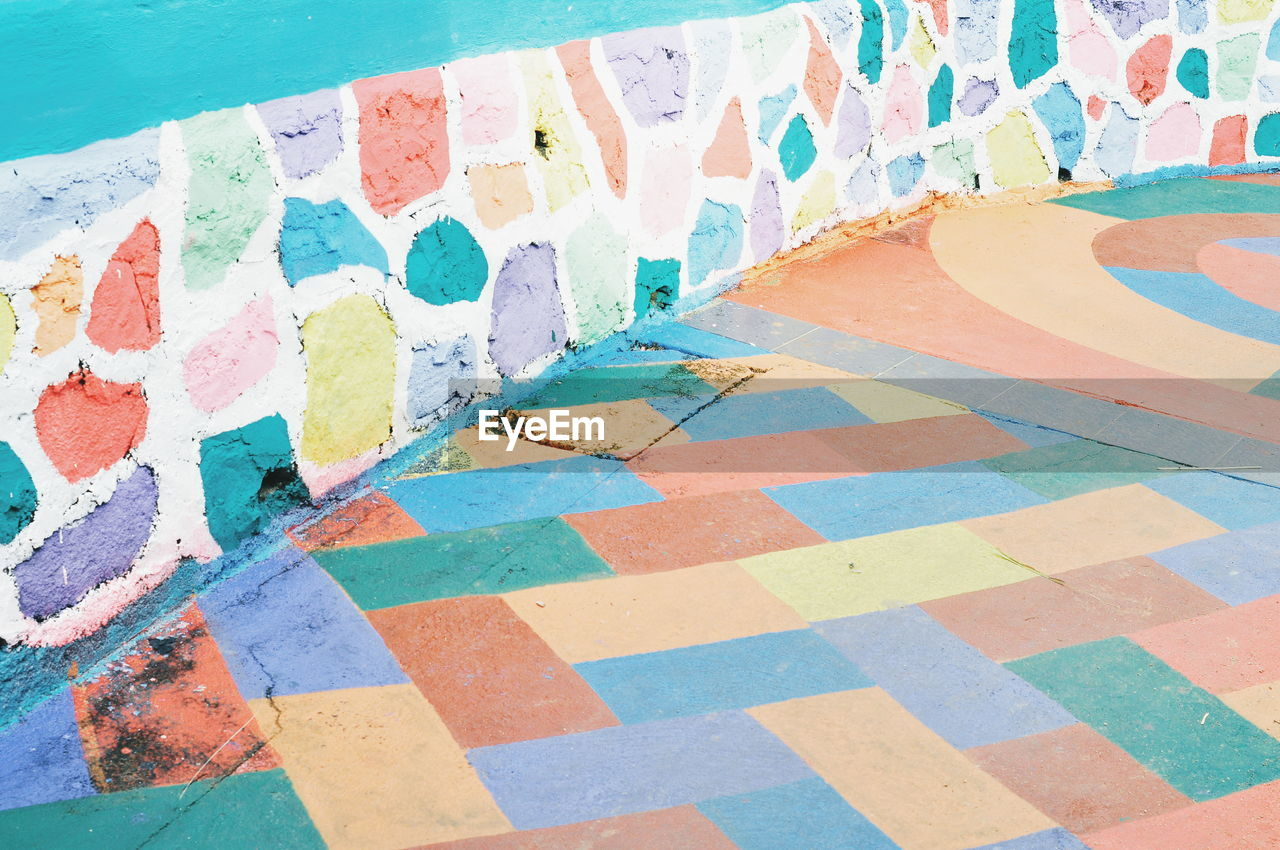 multi colored, no people, pattern, tile, water, pool, flooring, high angle view, tiled floor, swimming pool, architecture, day, wall - building feature, built structure, blue, art and craft, outdoors, footpath