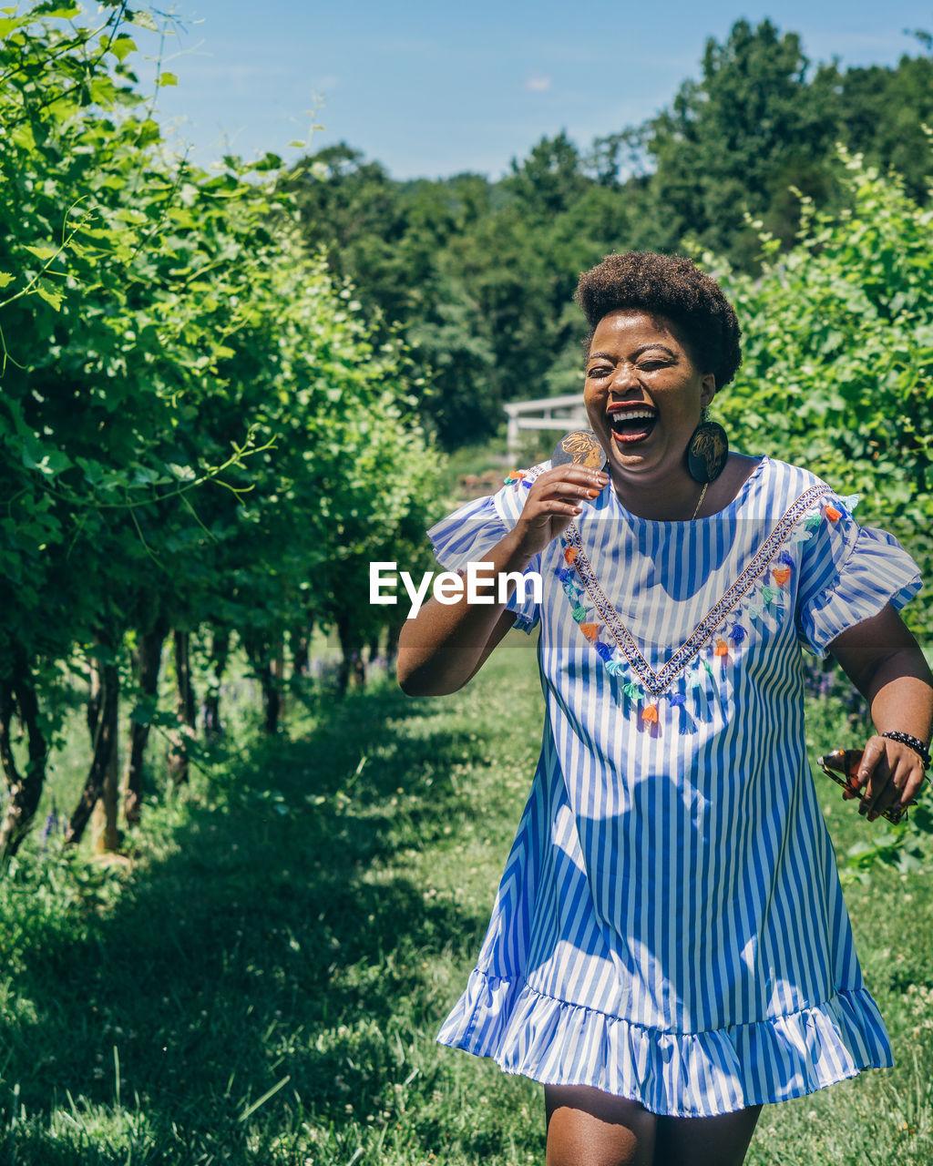 Smiling woman walking at vineyard