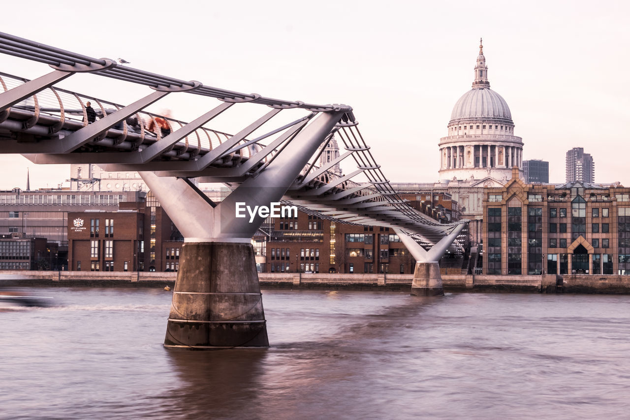 Low angle view of bridge over river by historic building against sky