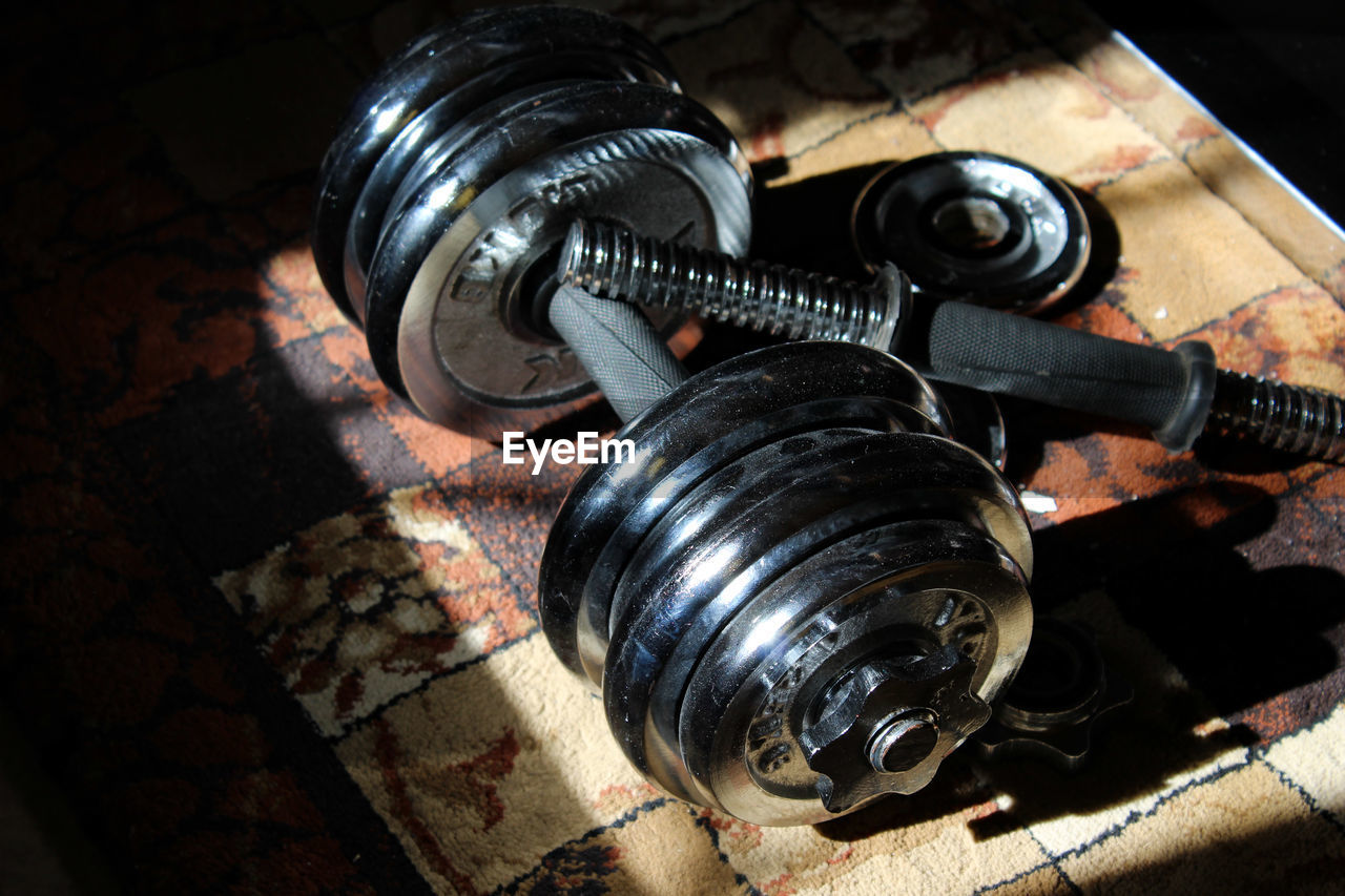 Close-Up Of Dumbbell And Barbell On Carpet