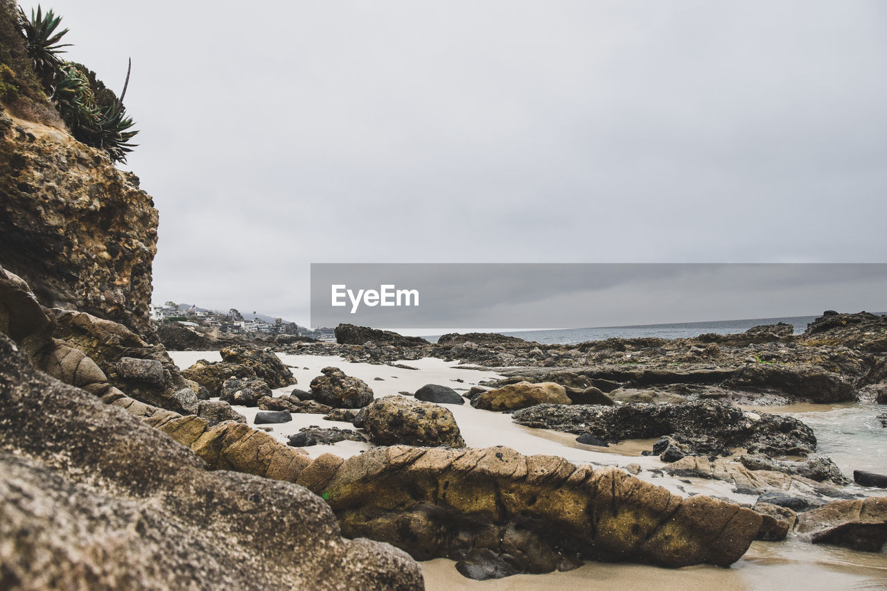 rock - object, nature, rock formation, sea, beauty in nature, rough, no people, water, scenics, day, sky, outdoors, cliff, tranquility, horizon over water, close-up