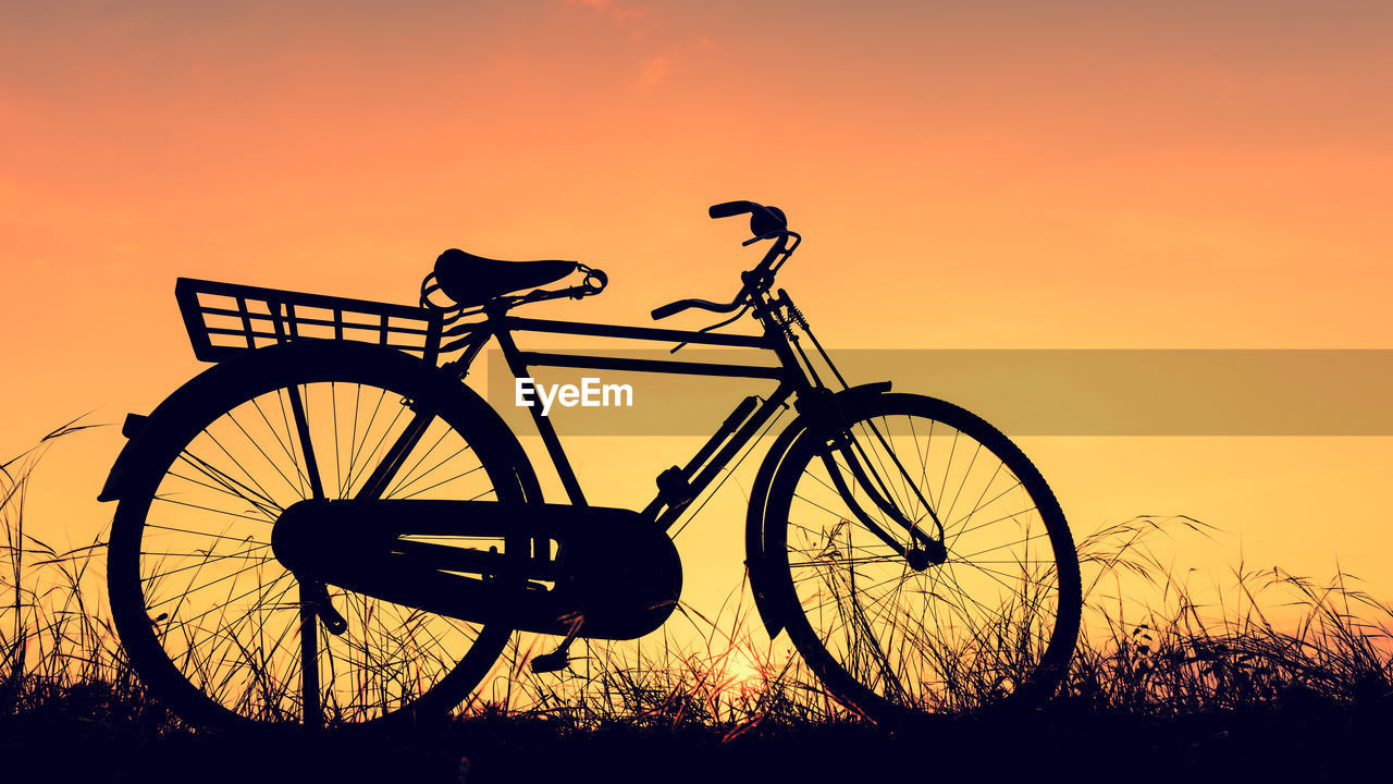 sunset, transportation, sky, orange color, land vehicle, mode of transportation, bicycle, silhouette, nature, stationary, beauty in nature, no people, land, outdoors, scenics - nature, travel, non-urban scene, tranquil scene, field, plant, wheel