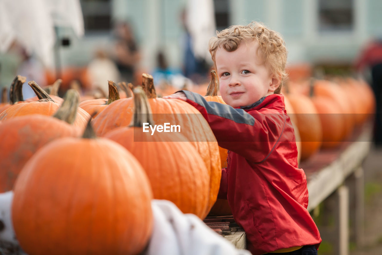 Portrait Of Boy Standing By Pumpkins