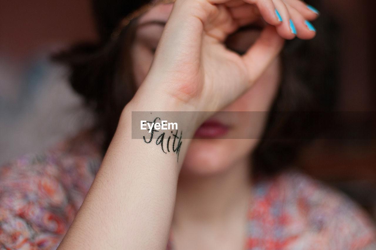 Close-Up Of Faith Text Tattoo On Woman Wrist