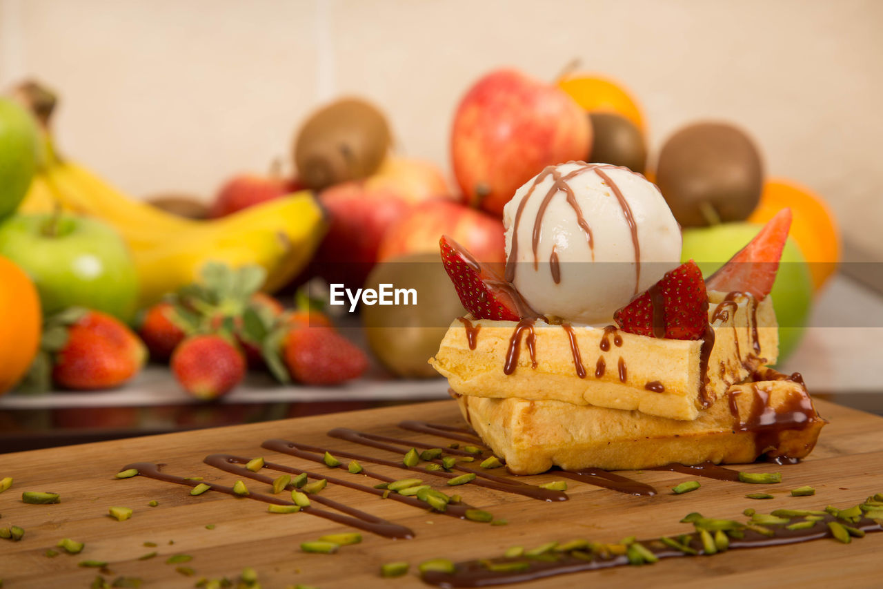Close-up of dessert against fruits on table