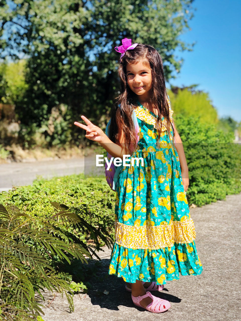 one person, plant, hairstyle, standing, fashion, girls, women, day, tree, nature, smiling, dress, sunlight, front view, looking at camera, child, portrait, long hair, leisure activity, childhood, hair, outdoors, floral pattern