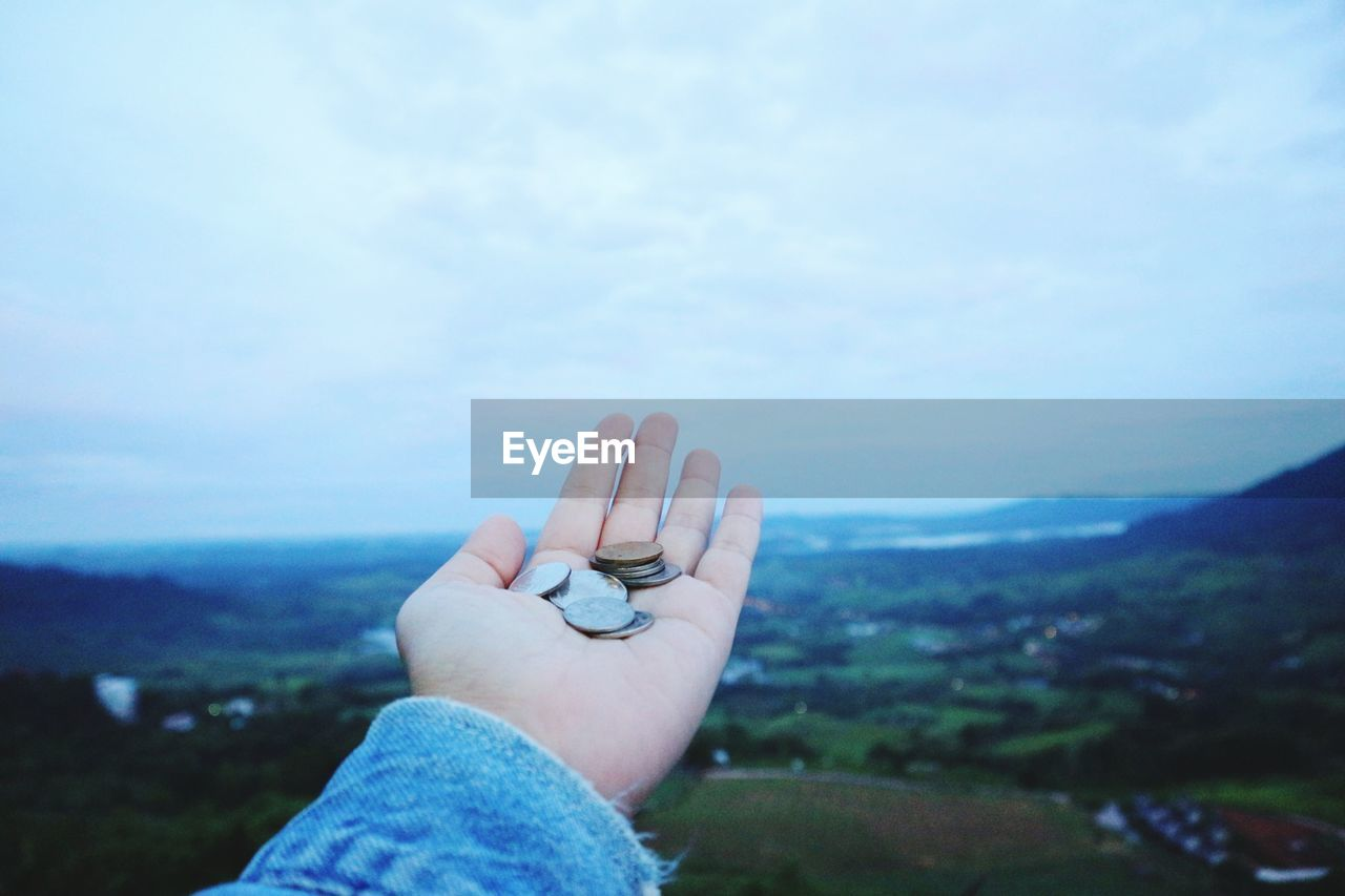 human hand, hand, human body part, one person, finger, human finger, real people, sky, personal perspective, body part, nature, day, leisure activity, focus on foreground, unrecognizable person, lifestyles, outdoors, mountain, scenics - nature