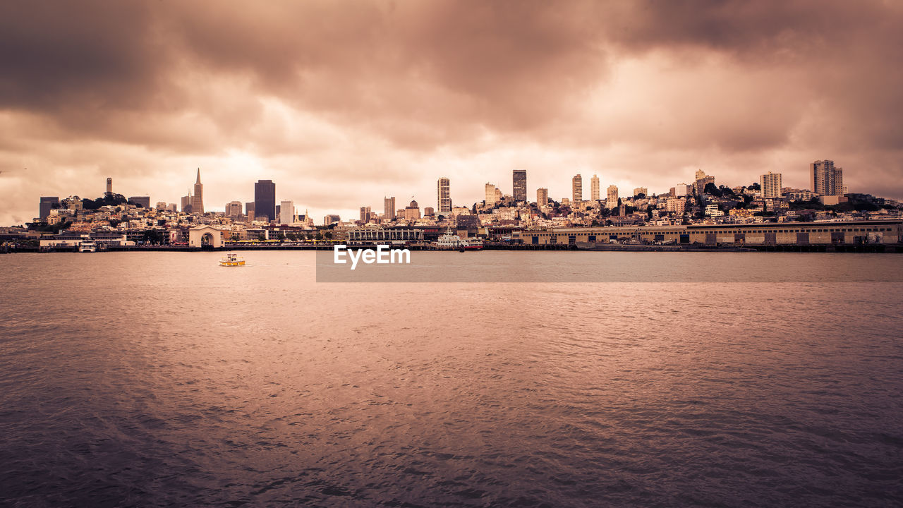 cloud - sky, sky, building exterior, water, city, built structure, waterfront, architecture, nature, cityscape, urban skyline, building, sea, no people, landscape, outdoors, sunset, office building exterior, skyscraper