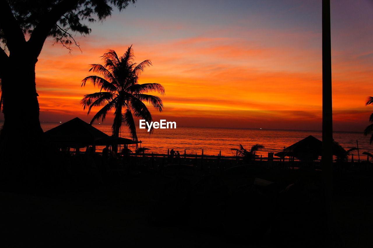 Silhouette beach against idyllic sky during sunset